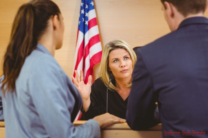 A Picture of a Judge Talking to Two People in Court.